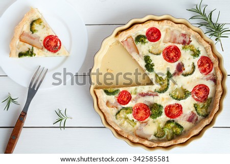 Sliced quiche lorraine tart pie traditional french food preparation recipe with tomatoes cheese bacon and broccoli in baking dish on white wooden table background. Rustic style and natural light. Top - stock photo