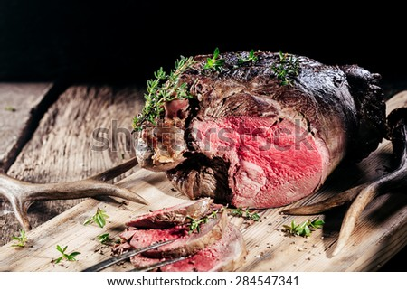 Sliced Rare Venison Roast Seasoned with Fresh Herbs and Served on Wooden Cutting Board with Deer Antlers - stock photo