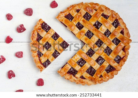 Sliced raspberry pie with fresh sugared raspberries on white table - stock photo