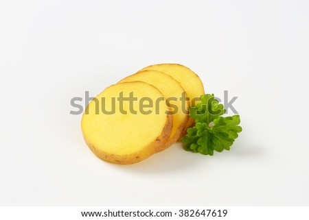 sliced raw potato and parsley on white background