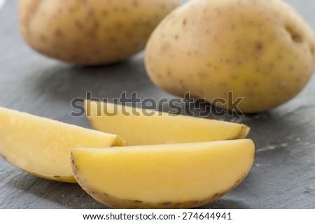 sliced raw potato on kitchen table - stock photo