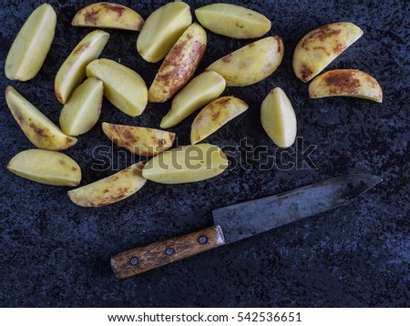 sliced raw potatoes and a knife against a dark marble background