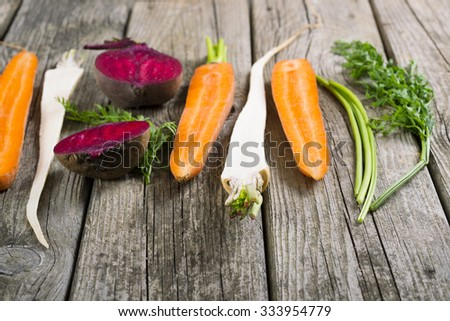 sliced raw vegetables: carrot, turnip, beetroot and parsley on old wooden table background - stock photo
