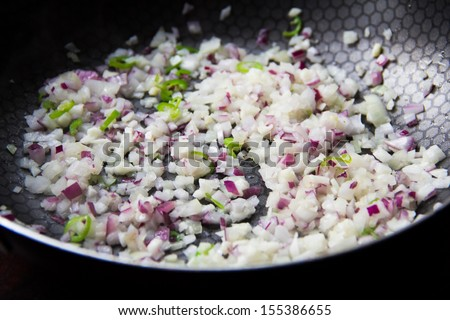 Sliced red and white onion passer in frying pan with garlic and green chilli - stock photo