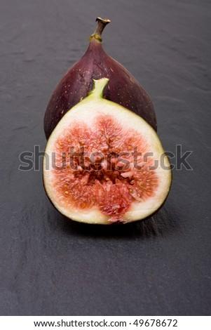 Sliced ripe figs isolated against dark slate background. - stock photo