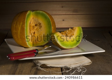 Sliced ripe spanspek, cantaloupe or sweet melon served on a platter on a table in front of a wooden wall with utensils for a healthy dessert - stock photo