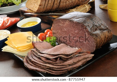 Sliced roast beef  with cheeses, breads and condiments - stock photo