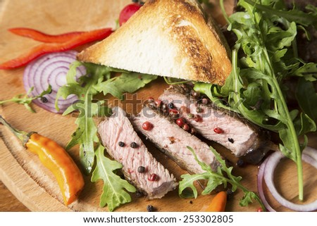 Sliced roast beef with vegetables and a slice of bread on a wooden plate - stock photo