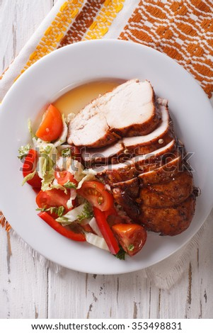Sliced roasted turkey breast and fresh vegetables on the plate close-up. vertical top view