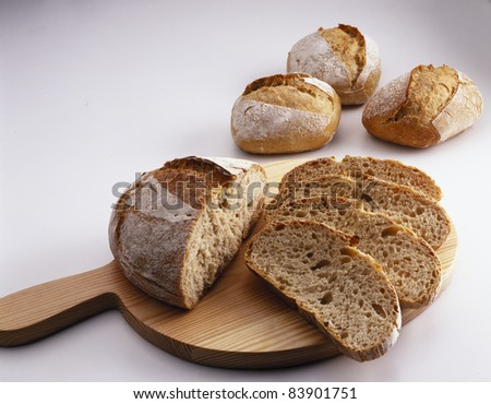 Sliced round bread loaf and individual bread loaves