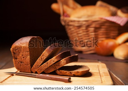 Sliced rye bread on cutting board and basket. Isolated over dark background. - stock photo