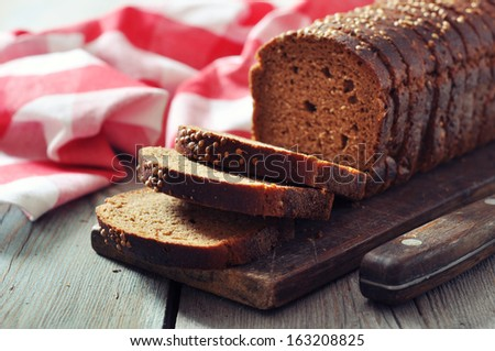 Sliced rye bread on cutting board closeup - stock photo