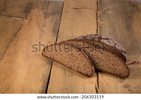 Sliced rye bread on wooden table, healthy eating - stock photo