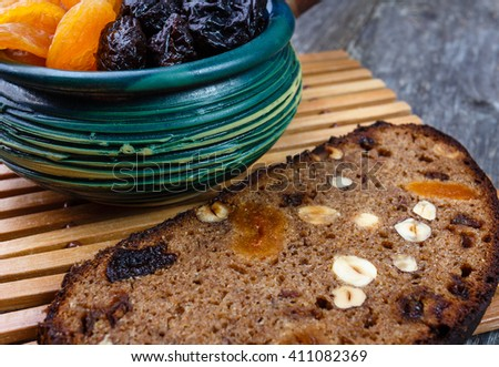 Sliced rye bread with prunes, dried apricots and hazelnut on old rustic table - stock photo