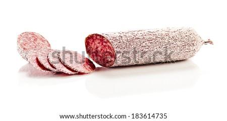 sliced salami on a white reflexive background - stock photo