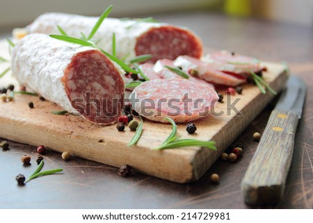 Sliced salami sausage on a wooden cutting board with herbs - stock photo