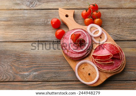 Sliced salami with cherry tomatoes, onion and spices on cutting board and wooden table background - stock photo