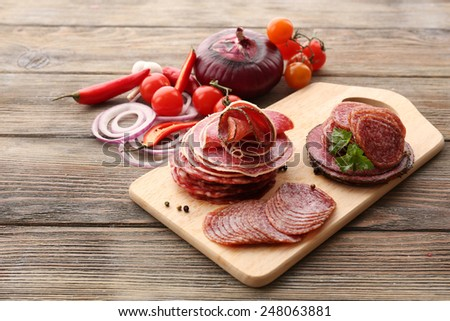 Sliced salami with chili pepper, cherry tomatoes, onion and spices on cutting board and wooden table background - stock photo
