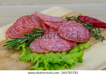 Sliced salami with salad leaves and rosemary - stock photo