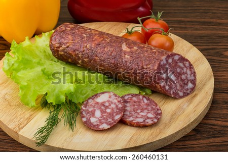 Sliced Salami with salad leaves on the wood background - stock photo