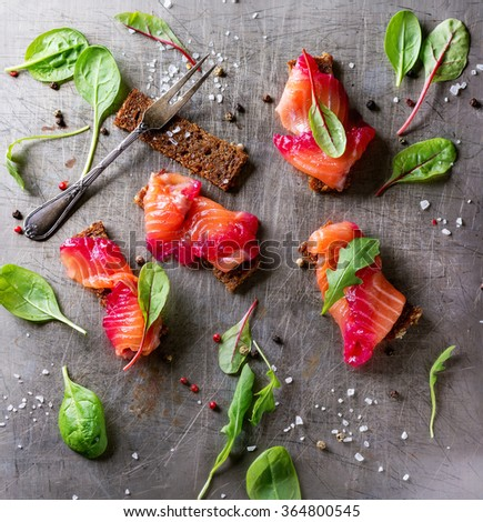 Sliced salmon filet, salted with beetroot juice, served on whole wheat toasts with salad leaves, sea salt and pepper and vintage fork over metal surface. Top view. Square image - stock photo