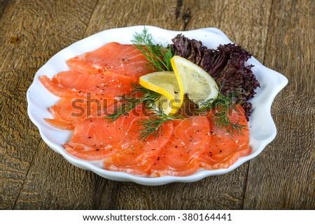 Sliced salmon sashimi served dill and lemon - stock photo