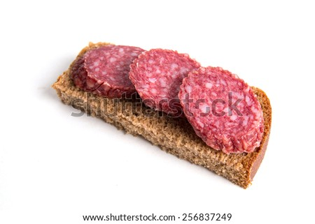 Sliced sausage on bread on a white background - stock photo