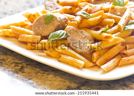 Sliced sausage with penne pasta and red tomato sauce with basil leaves - stock photo