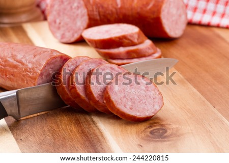 sliced sausages on chopping board  - stock photo
