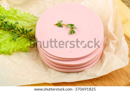 Sliced sausages with salad leaves and thyme on the wood background
