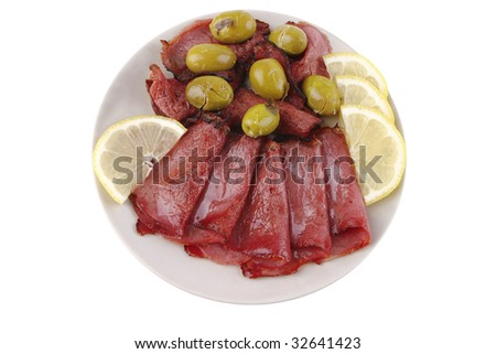 sliced served sausage with green olives and raw lemon