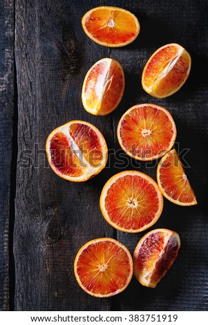 Sliced Sicilian Blood oranges fruits over old dark wooden background. Top view - stock photo