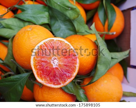 Sliced Sicilian blood red orange with leaf - stock photo
