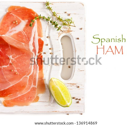 Sliced Spanish ham on an old white cutting board. - stock photo