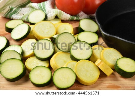 Sliced squash and zucchini by a cast iron skillet - stock photo