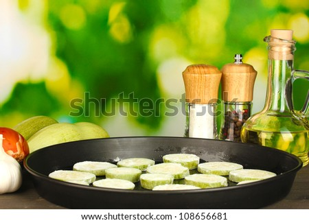 sliced squash in a pan on wooden table on green background close-up