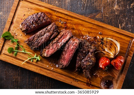 Sliced steak Ribeye with grilled onions and cherry tomatoes on cutting board on wooden background - stock photo