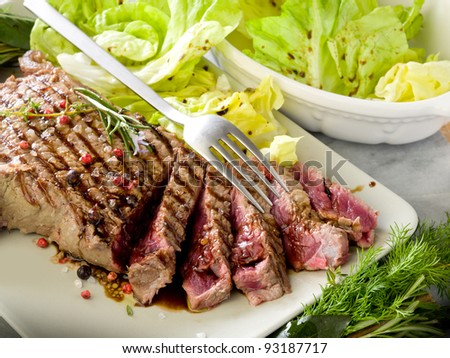 sliced steak with balsamic vinegar and green salad - stock photo