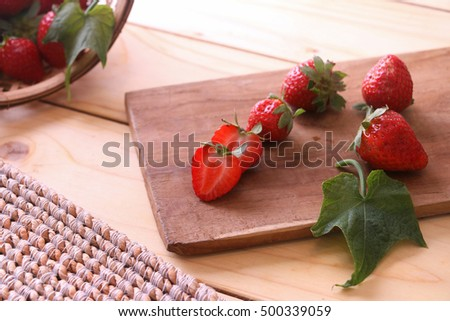 Sliced strawberries on a chopping board.