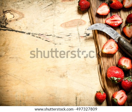 Sliced strawberries with the old knife on the Board.
