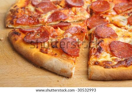 Sliced thin-crust pepperoni pizza - stock photo