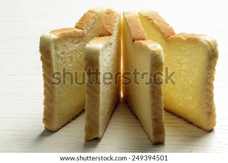 Sliced toast bread lies on a white surface of a table - stock photo