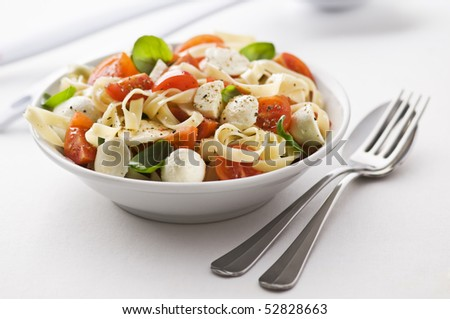 Sliced tomato and mozzarella with pasta close up - stock photo