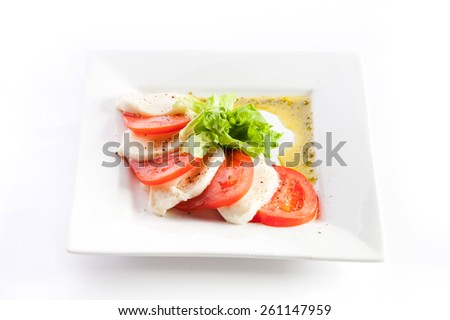 Sliced tomatoes and cheese with lettuce on a white background - stock photo