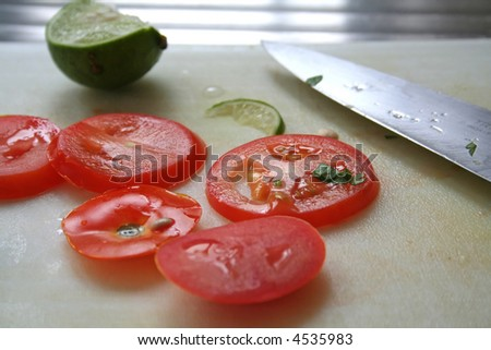 Sliced tomatoes and limes used in asian cuisine with knife on chopping board