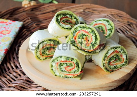 Sliced tortilla wrap with lunchmeat, ricotta and pesto sauce - stock photo
