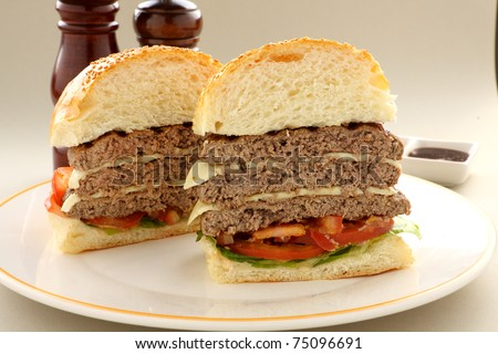 Sliced triple decker beef and cheese burger with salad ready to serve. - stock photo