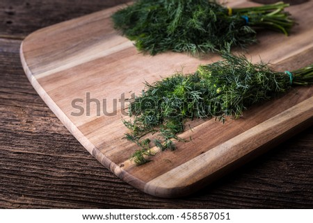Sliced twig of dill on a wooden board. Branch seasoning aromatic spice. - stock photo
