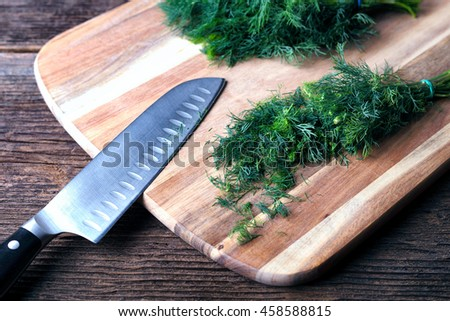 Sliced twig of dill on a wooden board with knife. Branch seasoning aromatic spice. - stock photo