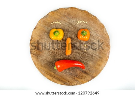 Sliced vegetables in form of a sad face with tears on white isolated background - stock photo